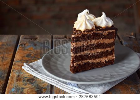 Piece Of Chocolate Cake Decorated With Rosettes Of Meringue Cream: Chocolate-nut Biscuit, Caramel Cr