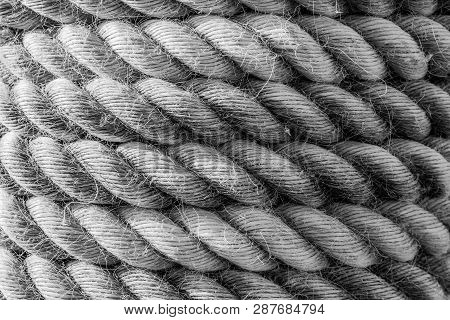 A Textured Background Of Coils Of Thick And Heavy Industrial Rope That Is Frayed, Worn And Weathered