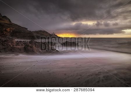 Stormy Sunrise At Bracelet Bay Over Mumbles Lighthouse And Bracelet Bay On The Gower Peninsula In Sw