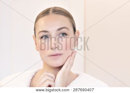 Genuine beauty of a young woman with natural makeup, applying anti aging cream, nice female with perfect clear facial skin, beauty and health care concept poster