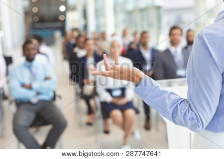 Rear view of caucasian female speaker speaks to diverse business people sitting in front her in a business seminar in a conference room