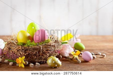 poster of Easter composition with colorful Easter eggs in nest ,spring flowers and branches of pussy willows on wooden background. Easter card with copy space.