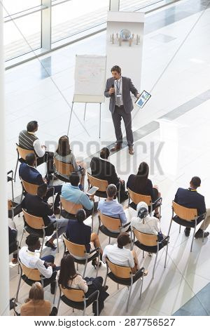 High angle view of middle-aged Caucasian businessman speaking while holding digital tablet and microphone at conference. Group of diverse business people sitting on wooden chairs while listening to
