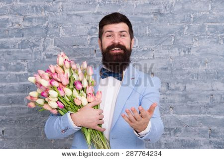Macho Getting Ready Romantic Date. Tulips For Sweetheart. Romantic Gift. Man Well Groomed Tuxedo Bow