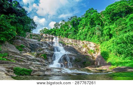Beautiful Waterfall At The Mountain With Blue Sky And White Cumulus Clouds. Waterfall In Tropical Gr