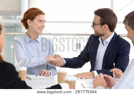 Millennial Businesspeople Gathered In Boardroom Starting Negotiations Shaking Hands