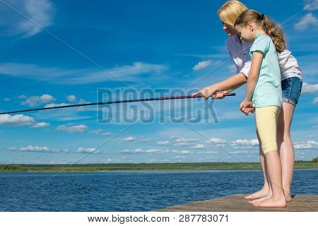 Mom Teaches Her Daughter To Fish, Outdoors, Standing On The Pier, Against The Blue Sky
