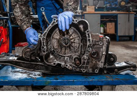 A Close-up Of A Young Man Repairman In A Working Uniform Of Cars Is Repairing An Automatic Gearbox O