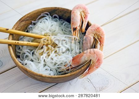 Chinese Diet Noodles With Shrimps In A Wooden Bowl On A Wooden Table, Next To A Bowl With Soy Sauce.