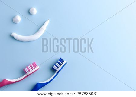 Blue And Pink Toothbrushes On Blue And A Toothpaste Smiling Face. Toothpaste In A Form Of A Smiling