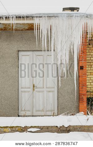 Huge Icicles Hang From The Roof Of An Abandoned House With Wooden Door.