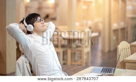 Young Asian Carefree Guy With Glasses Enjoy Listening To Music By Headphones Relaxing After Working