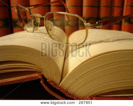 Open Book With Glasses On Pages