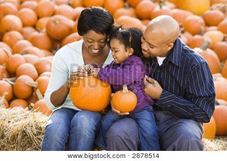 Family Holding Pumpkins.