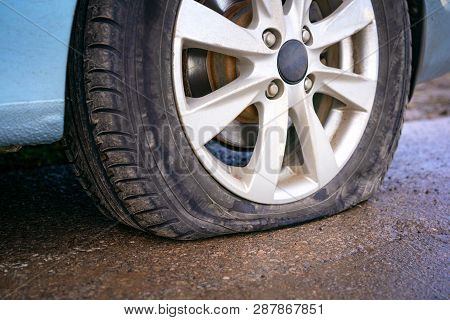 Flat Tire Of Blue Car On The Road Waiting For Repair.  Car Tire Leak Because Of Nail Pounding.