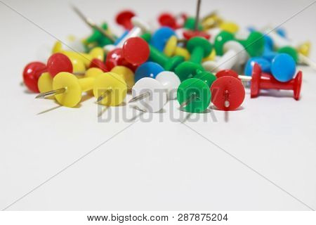 Colorful yellow, green, red pushpins on white background poster