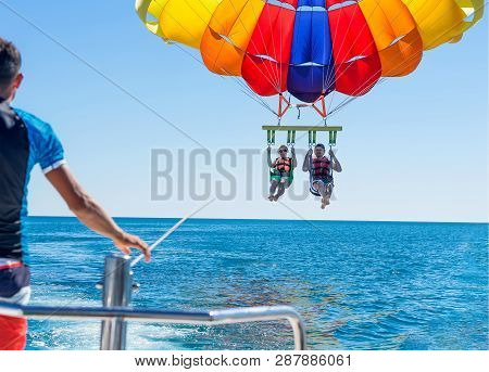 Happy Couple Parasailing On Miami Beach In Summer. Couple Under Parachute Hanging Mid Air. Having Fu