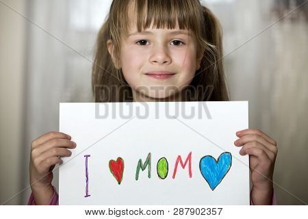 Cute Child Girl Wit Sheet Of Paper With Colorful Crayons Painted Words I Love Mom. Art Education, Cr