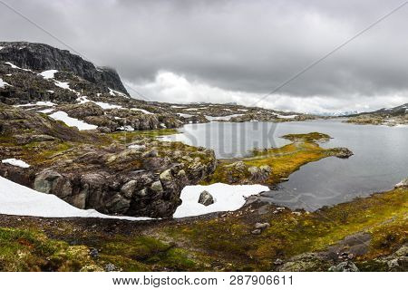 Spring norvegian andscape with lake and snowy mountains on background