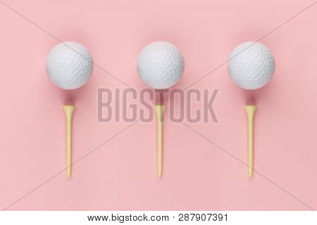 Abstract golf concept with three wooden tee and white golf ball isolated on pink