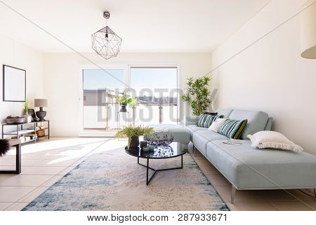 Modern living room with designer sofa and coffee table. Window with view. Nobody inside
