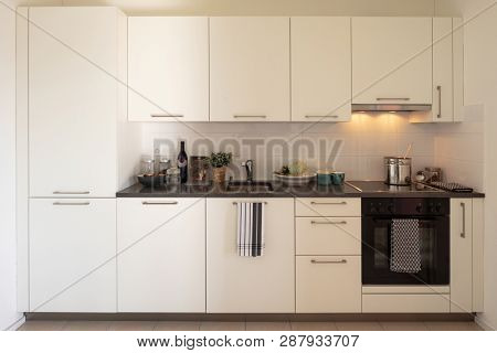 Front view of white modern kitchen with lights on. Nobody inside