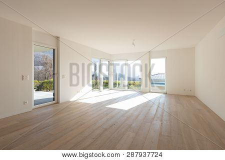 Empty white living room interior with parquet. Large windows. Nobody inside