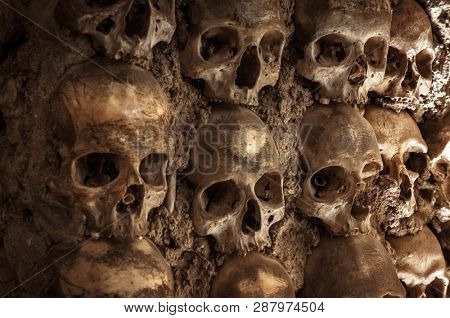 Skull and human bones. Cemetery ancient wall pattern. Horror dark chapel. Death pattern concept. Scary skeleton background. Old catacomb grave full of skulls. Plague tomb