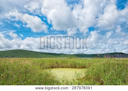 Scenic View Of Summer Sky, Hills And Marsh Near Stark Strait, Russia. Nature And Tourism Theme.