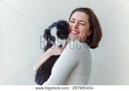 Smiling Young Attractive Woman Embracing Cute Puppy Dog Border Collie Isolated On White Background.