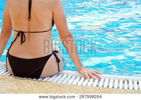 A Young Woman Sits On The Edge Of The Pool Back View. Back View Of Young Woman In Bikini Sitting On
