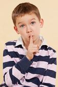 The secret. Don't tell anyone. Young boy with finger over his mouth isolated on neutral background. Facial expressions concept. Psst poster