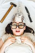 Silly paranoid woman wears tinfoil hat and sleeps with weapon and different glasses because of paranoia. Concept of anxiety and fears of reading thoughts by aliens different radiation and other danger poster