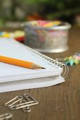 yellow pencil on a notebook with paper clip on a wooden table poster