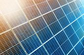 Close-up surface of lit by sun blue shiny solar photo voltaic panels. System producing renewable clean energy. Renewable ecological green energy production concept. poster