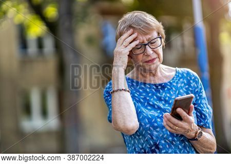 Stressed senior woman using mobile phone outdoors