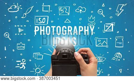 Hand taking picture with digital camera and PHOTOGRAPHY IDEAS inscription, camera settings concept