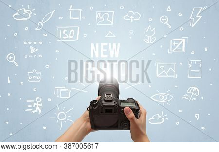 Hand taking picture with digital camera and NEW PHOTO inscription, camera settings concept