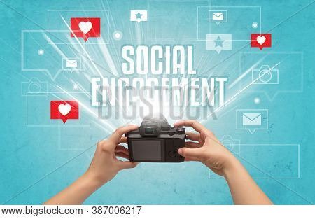 Close-up of a hand taking photos with SOCIAL ENGAGEMENT inscription, social media concept
