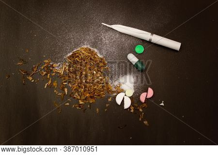 Cigarette And Pills On A Black Background. Tobacco On The Black Table. Pills, Cigarette, Tobacco On