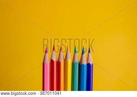 Seven Colored Pencils In The Center In Row Order And In Gradient Color, With Colors Like Pink, Blue,