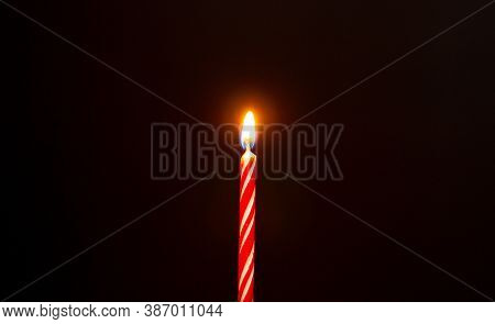 Red Birthday Candle. Birthday Candle On Black Background. Burning Birthday Candle On Black Texture