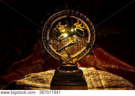 Golden Idol Of The Hindu God Lord Nataraja With Back Lighting Placed On A Red Cloth