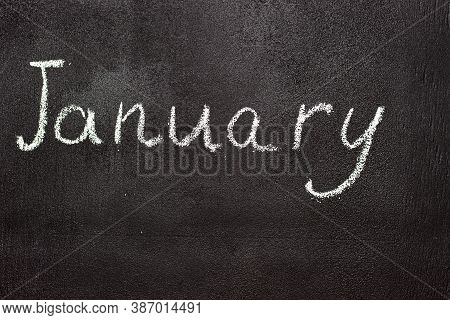 Month Written In White Chalk On A Chalkboard. The Month Depicted On The Chalkboard Is January