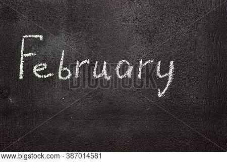 Month Written In White Chalk On A Chalkboard. The Month Depicted On The Chalkboard Is February