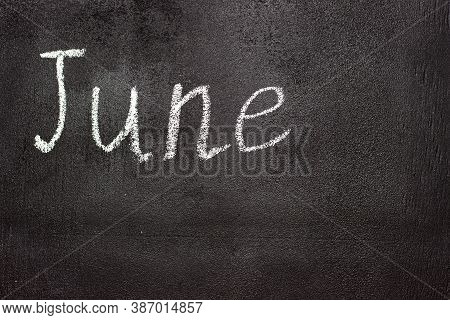 Month Written In White Chalk On A Chalkboard. The Month Depicted On The Chalkboard Is June