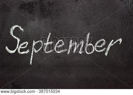 Month Written In White Chalk On A Chalkboard. The Month Depicted On The Chalkboard Is September