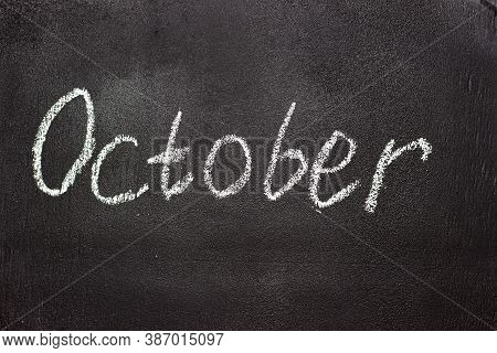 Month Written In White Chalk On A Chalkboard. The Month Depicted On The Chalkboard Is October