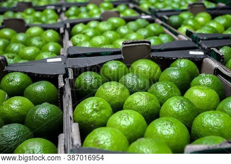 Fresh Ripe Limes In Cardboard Boxes At An Open-air Vegetable Market. Wholesale. Background From Plum