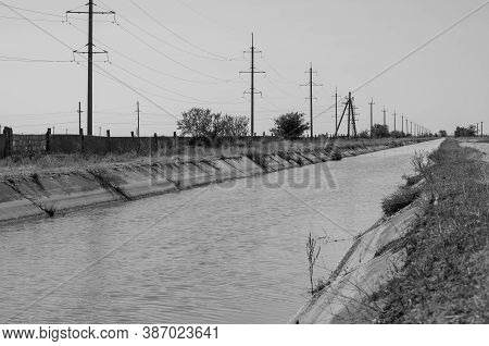 Irrigation Agricultural Channel With Water. Power Line Along The Canal For Irrigation. Summer Sunny